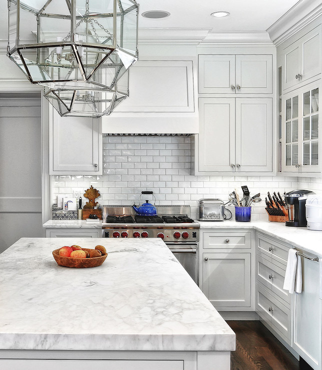 Classic kitchen design with marble countertop and subway tiles - stainless steel stove