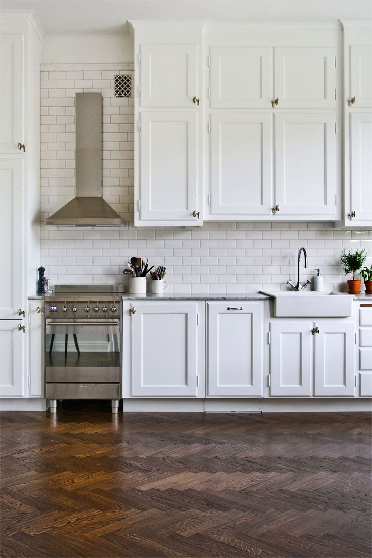 White kitchen design with a rustic floor